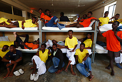 Would-be immigrants sit in their dormitory at the Safi barracks detention centre for immigrants, which currently holds around 600 detainees, in Safi, outside Valletta July 19, 2013. Would-be immigrants who land in Malta face mandatory detention which can last for 18 months but figures show nearly half are allowed out sooner, following the granting of refugee status or humanitarian protection, according to official sources.  Malta will be given concrete assistance by the European Commission to return failed asylum seekers to their country of origin, the government has announced.<br />REUTERS/Darrin Zammit Lupi (MALTA - Tags: SOCIETY IMMIGRATION TPX IMAGES OF THE DAY) - RTX11S66