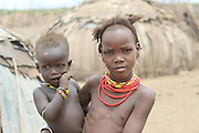 Africa, Ethiopia, Omo Valley, Daasanach tribe young girl carries her baby brother