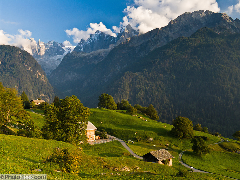 "Roads meander in green pastures near Soglio village beneath rugged granite mountains of Sciora Group in the Bregaglia Range, Switzerland, the Alps, Europe. Published in Ryder-Walker Alpine Adventures ""Inn to Inn Alpine Hiking Adventures"" Catalog 2008."