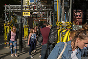 Busy street corner with yellow scaffolding protection sleeves and passing pedestrians on Long Acre near Covent Garden, on 1st September 2017, in London, England.