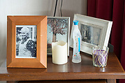 small table stand with framed family photos and Lourdes water