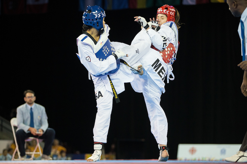 Paige McPherson (L) of the United States and Victoria Heredia of Mexico trade kicks during their gold medal contest in women's taekwondo -67 kg division at the 2015 Pan American Games in Toronto, Canada, July 21,  2015.  AFP PHOTO/GEOFF ROBINS