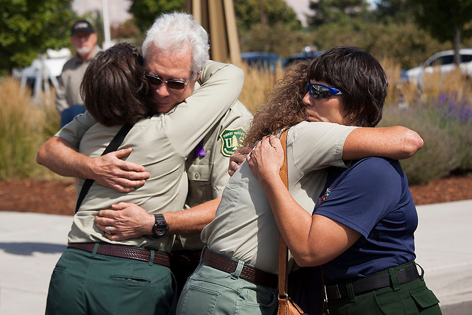 Members of the U.S. Forest Service and other agencies embrace during a memorial for U.S. Forest Service firefighters Tom Zbyszewski, Andrew Zajac, and Richard Wheeler, who died fighting the Okanogan Complex fire, in Wenatchee, Washington August 30, 2015. So far this year, U.S. wildland blazes have claimed the lives of at least 13 firefighters, four more than were killed in the line of duty during all of 2014. REUTERS/David Ryder