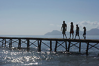Silhouettes of parents and children (6-11) walking on jetty