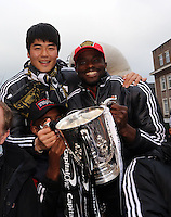 Pictured L-R: Ki Sung Yueng and Roland Lamah.  Tuesday 26 February 2013..Re: Thousands of Swansea City fans have lined the city's streets to welcome home their League Cup-winning heroes...The Swans, who are celebrating their centenary this season, beat Bradford City 5-0 in Sunday's Capital One Cup final at Wembley...The open-top bus parade started outside the Dragon Hotel at 4.30pm and finish at the Brangwyn Hall through the Kingsway and St Helen's Road before reaching its final destination about an hour later.