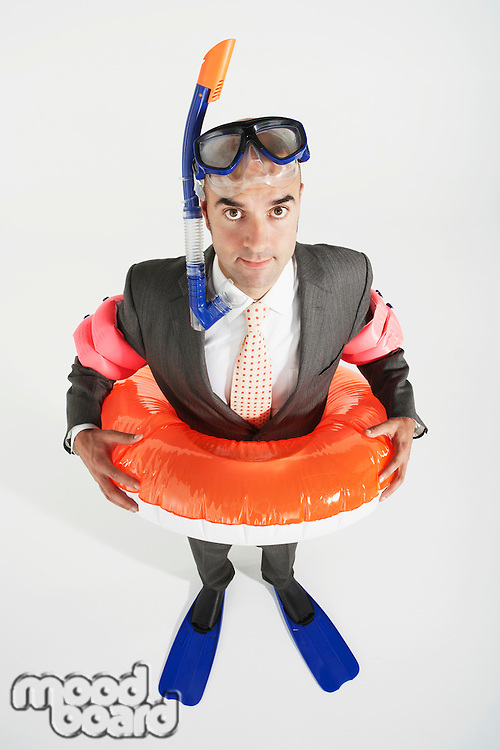 Middle-aged businessman in flippers inflatable rubber ring snorkel and goggles