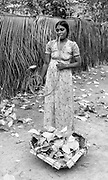 Woman smoking tobacco in a water pipe. She has been collecting betel leaves. Thoddu island. Note cadjan fence in the background. 1990