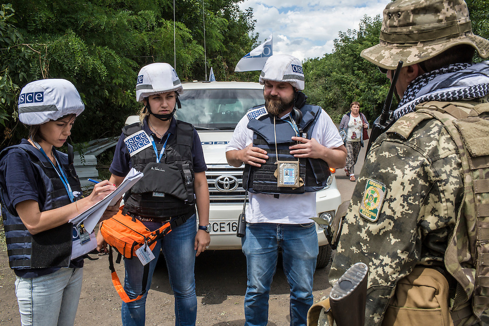 ZAITSEVE, UKRAINE - JULY 9, 2016: OSCE monitoring team members Bilyana Petrovka, a monitoring officer from Bulgaria, left, Kseniya Bilozerova, a language assistant from Ukraine, center, and patrol leader Piotr Szczepaniak from Poland speak with a Ukrainian soldier to determine patterns of movement by civilians through a crossing point between Ukrainian government-controlled territory and the rebel-held Donestk People's Republic at a checkpoint in Zaitseve, Ukraine. The mission tracks violations of the Minsk-II ceasefire agreement, among other tasks. CREDIT: Brendan Hoffman for The New York Times