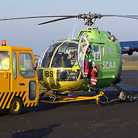 A unique 'Blue Light' assembly to place today at Perth Airport (12.02.15), home of Scotland's Charity Air Ambulance. SCAA will soon mark it's 500th emergency callout and to commemorate this landmark and to pay thanks to and acknowledge the working relationship with other vital services - crews, vehicles and aircraft who work alongside SCAA within the emergency 999 response network in Scotland gathered for this photograph. The line-up including police, ambulance, fire & rescue, coastguard, moutain rescue teams, RNLI, BASICS Scotland, First Responders and Royal Navy Search & Rescue. Pictured shows Helimed 76 being towed into place<br /> Picture by Graeme Hart.<br /> Copyright Perthshire Picture Agency<br /> Tel: 01738 623350  Mobile: 07990 594431