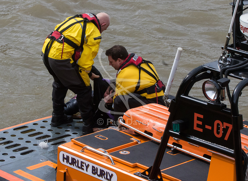 Westminster, London, March 29th 2017. A person, still believed to be alive, is pulled by RNLI rescuers from the River Thames. It is not known if the man is the one who is reported to have jumped earlier.