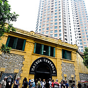 In the foreground is the main entrance to Hoa Lo Prison, with tourists standing on the sidewalk. At back is the modern new building that has been built on the bulk of the space formerly occupied by the prison. Hoa Lo Prison, also known sarcastically as the Hanoi Hilton during the Vietnam War, was originally a French colonial prison for political prisoners and then a North Vietnamese prison for prisoners of war. It is especially famous for being the jail used for American pilots shot down during the Vietnam War.