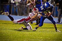 Sandpoint High's Joe Duarte tries to hang onto Matt Lambert from Coeur d'Alene High during the first half of Friday's game. The Vikings defeated the Bulldogs 55-7.