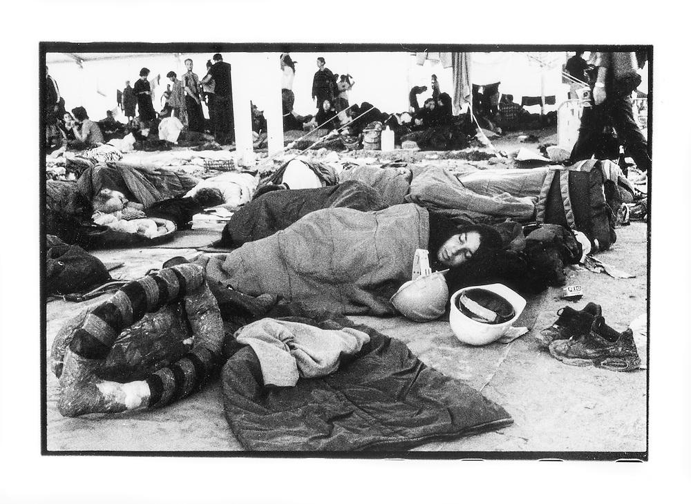 Proteste contro il summit del G8, Genova luglio 2001. Venerdì 20 luglio, corteo dei Disobbedienti. Manifestante dorme con accanto caschi e corazze. Campeggio dello stadio Carlini.