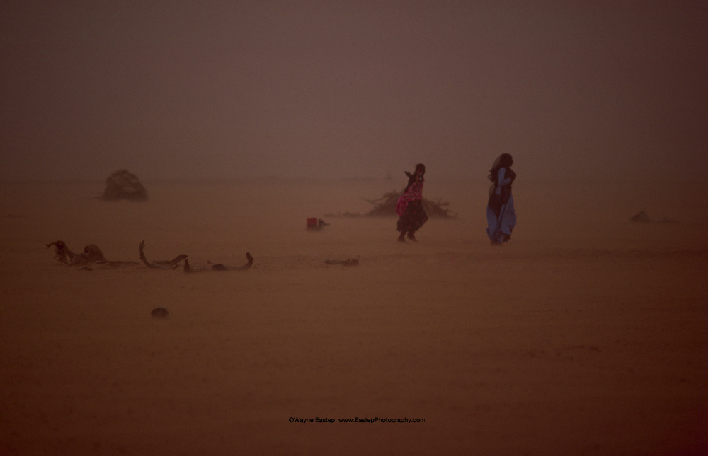 Two Shammar women make their way back to their tent in a sandstorm in the Nafud Desert, Saudi Arabia.