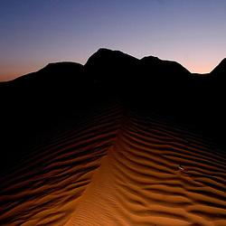 Sand dunes are illuminated at dusk near Gallup, New Mexico.