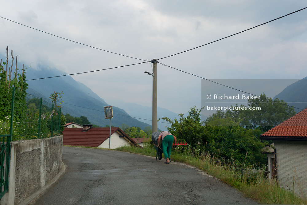 An elderly local woman hunches over a small cart transporting freshly mown grass in a rural mountainside Slovenian village, on 21st June 2018, in Borjana, near Kobarid, Slovenia.