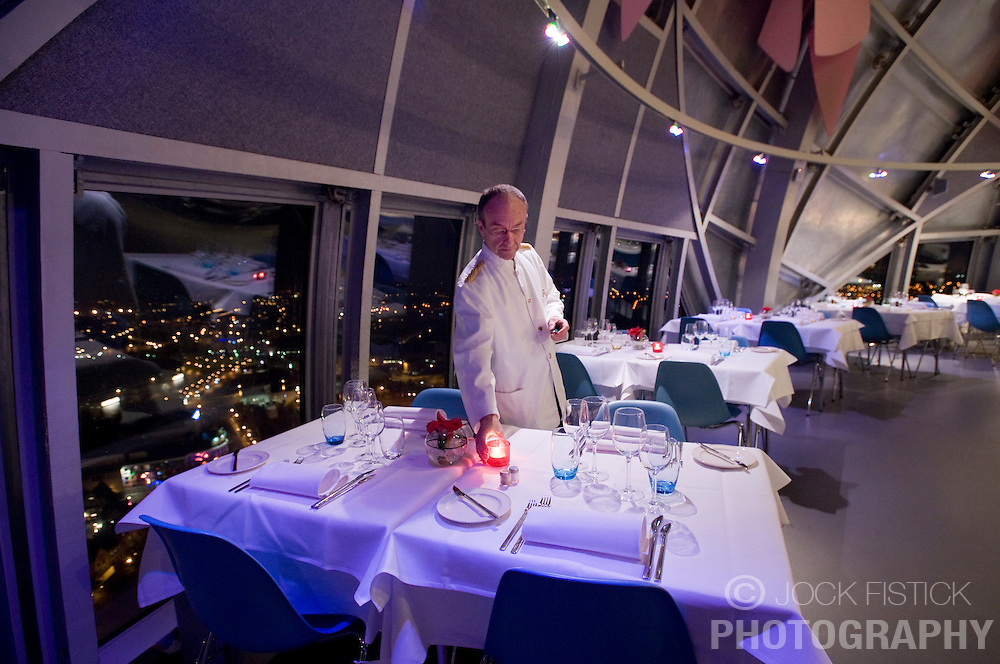 BRUSSELS, BELGIUM - FEB-4-2008 - Dany Deschuyteneer, chef de rang,  prepares his tables for the evening service at the Atomium Restaurant,  located in the top sphere of the Atomium. The Atomium is a monument built for Expo '58, the 1958 Brussels World's Fair. Designed by André Waterkeyn, it is 103-metre (335-feet) tall, with nine steel spheres, each 18 meters in diameter, connected so that the whole forms the shape of a unit cell of an iron crystal magnified 165 billion times. Tubes which connect the spheres along the 12 edges of the cube and from all eight vertices to the centre; these tubes enclose escalators containing exhibit halls and other public spaces. (PHOTO © JOCK FISTICK)