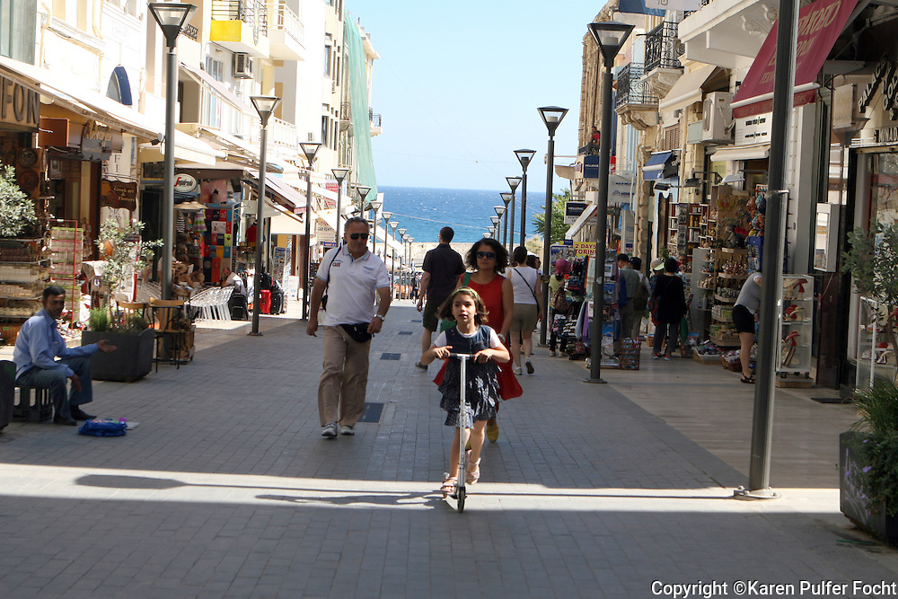 June 1, 2014 - A child rides up a main street ,on a scooter, on the Greek island Crete.