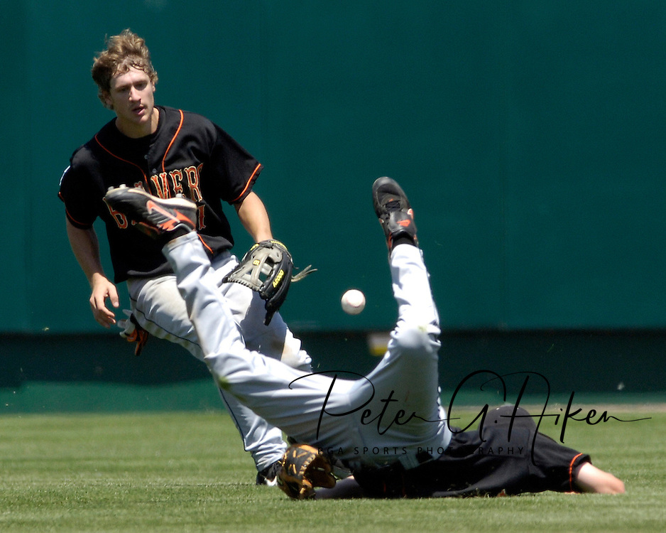Oregon State second basemen Chris Kunda (front) hits the ground hard, after missing a short fly ball to right-center field, as Beaver center fielder Tyler Graham moves in for the ball.  Oregon State eliminated Georgia with a 5-3 win at the College World Series at Rosenblatt Stadium in Omaha, Nebraska, June 19, 2006.