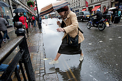 © licensed to London News Pictures. London, UK 09/04/2012. A woman trying to avoid stepping in a pool on the road on Regents Street in central London, this afternoon (09/04/12). Photo credit: Tolga Akmen/LNP