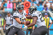 Sunday, October 6, 2019; Charlotte, N.C., USA;  Jacksonville Jaguars quarterback Gardner Minshew (15) hands the ball off to running back Leonard Fournette (27) during an NFL game against the Carolina Panthers at Bank of America Stadium. The Carolina Panthers beat the Jacksonville Jaguars 34-27. (Brian Villanueva/Image of Sport)