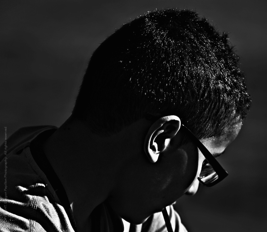 black and white side view of male youth looking down with strong light contrast on eye socket and ear