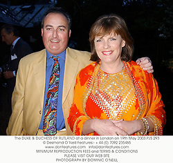 The DUKE & DUCHESS OF RUTLAND at a dinner in London on 19th May 2003.PJS 293