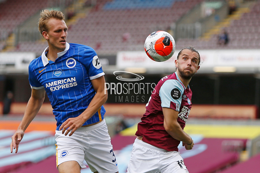 Brighton and Hove Albion defender Dan Burn (33) and Jay Rodriguez of Burnley (19)  contest an aerial ball during the Premier League match between Burnley and Brighton and Hove Albion at Turf Moor, Burnley, England on 26 July 2020.