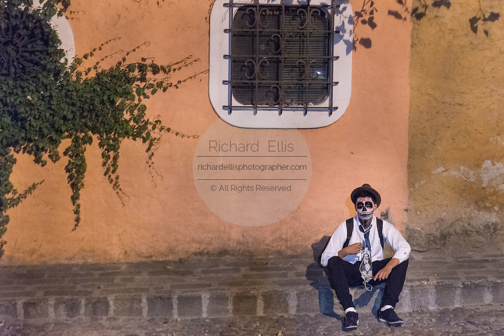 A young man dressed as the dapper skeleton rests along a street during the Day of the Dead festival November 1, 2016 in San Miguel de Allende, Guanajuato, Mexico. The week-long celebration is a time when Mexicans welcome the dead back to earth for a visit and celebrate life.