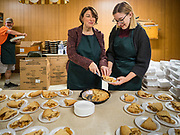 28 NOVEMBER 2019 - DES MOINES, IOWA: US Senator AMY KLOBUCHAR (D-MN), left, and her daughter ABIGAIL BESSLER cut pies at the dessert table in the South Des Moines Community Center. Sen Klobuchar served Thanksgiving lunches to people at the center. Sen. Klobuchar is campaigning to be the Democratic nominee for the US Presidency. Iowa holds the first selection event of the Presidential election cycle. The Iowa caucuses are Feb. 3, 2020.               PHOTO BY JACK KURTZ
