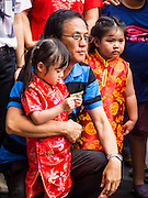 """19 FEBRUARY 2015 - BANGKOK, THAILAND: A man and his daughters watch a lion dance troupe during Chinese New Year festivities in Bangkok. 2015 is the Year of Goat in the Chinese zodiac. The Goat is the eighth sign in Chinese astrology and """"8"""" is considered to be a lucky number. It symbolizes wisdom, fortune and prosperity. Ethnic Chinese make up nearly 15% of the Thai population. Chinese New Year (also called Tet or Lunar New Year) is widely celebrated in Thailand, especially in urban areas that have large Chinese populations.    PHOTO BY JACK KURTZ"""