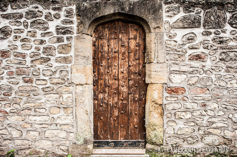 An old wooden door embeded into the stone wall fortifications of the Bishop's Palace in Wells, Somerset, England.