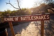 Sign warning of rattlesnakes along the coast of the Salton Sea at sunrise Imperial Valley, CA.