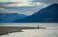 A lone fisherman below the rugged Southern Alps above Lake Wakatipu, on New Zealand's south island.