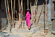Indian woman in sari carrying cement while working on construction site at Khore village in Rajasthan, India