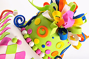 Detail of colorful Birthday Cake with green, pink, blue, orange and yellow harlequin decorations, balls and curlicues