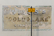 A detail of old advertising for a cigarette brand from decades ago called Will's whose product was 'Goldflake', on 19th July 2020, in Whitstable, Kent, England. W.D. & H.O. Wills was a British tobacco importer and manufacturer formed in Bristol, England. W.D. & H.O. Wills was founded in 1786 and was the first UK company to mass-produce cigarettes. It was one of the founding companies of Imperial Tobacco along with John Player & Sons.