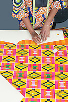 Midsection of female fashion designer marking pattern with chalk on fabric textile