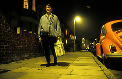 Woman walking alone at night, London UK