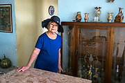 """Ismaela Perez, 76, is photographed in her home in Havana. She came to Havana the year of the revolution and became involved in a social organization teaching literacy. During the missile cirsis, she was mobilized with a group of women in a leadership role in the mountains. """"We were totally isolated and had no idea what was happening with the crisis. We got a lot of distorted news and didn't know if the war or the world had ended,"""" she explains. While she married, she couldn't have children. I was sad that I couldn't have children but in every student, I saw a child that I could nurture and I always felt my career was fulfilling,"""" she says. """"Cuban women are brave and show solidarity between each other and women in other countries. I think Cuban women face many difficulties but remain stoic,"""" she adds."""
