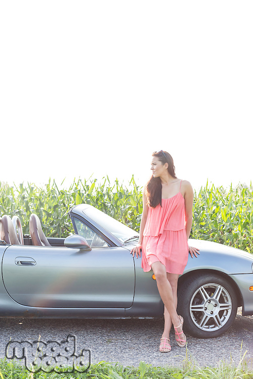 Full-length of woman leaning on convertible against clear sky