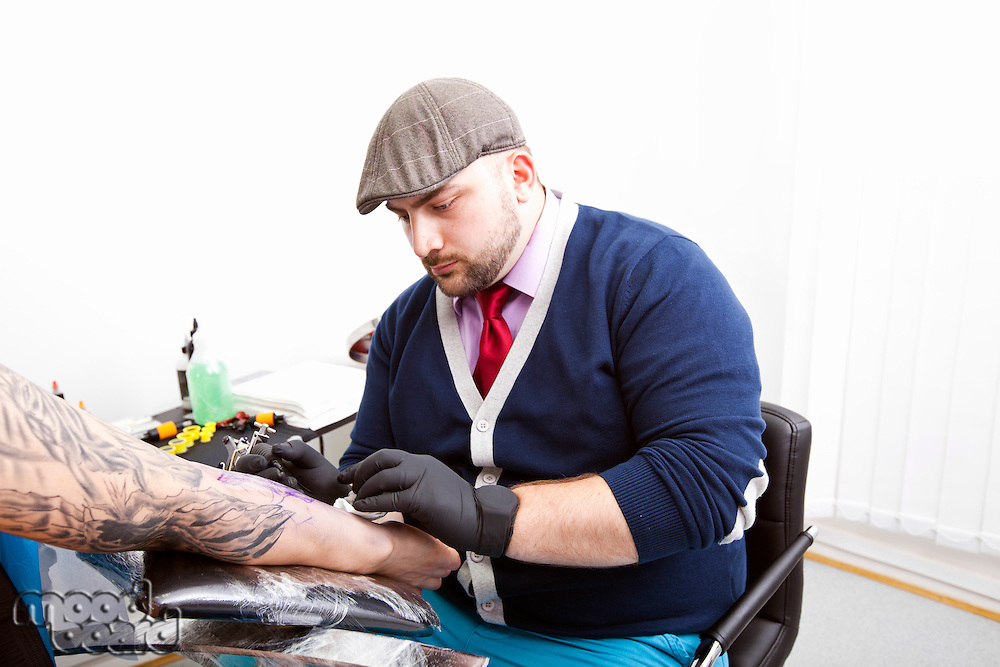 Young artist tattooing man's arm in tattoo parlor