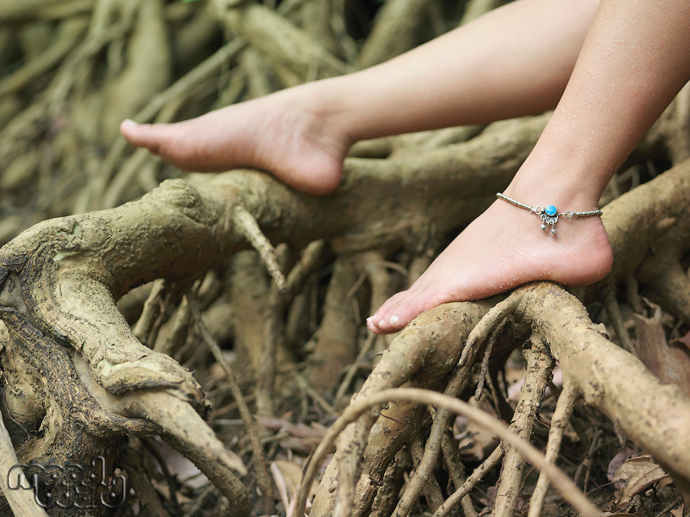Young woman sitting on tree roots close-up on foot
