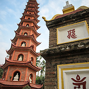 A tower with statues and part of the main gate at Tran Quoc Pagoda on a small island on West Lake (Ho Tay). Originally built in the 6th century on the banks of the Red River, a changing course of the river forced the pagoda to be relocated in 1615 to Golden Fish (Kim Ngu) islet on the lake.