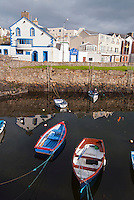 Colorful rowing boats moored in the seaside resort town of Portrush in County Antrim, Northern Ireland.