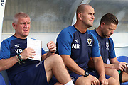 AFC Wimbledon coach Vaughan Ryan, AFC Wimbledon coach Mark Robinson and AFC Wimbledon goalkeeping coach Ashley Bayes sitting on the bench prior to kick off during the Pre-Season Friendly match between AFC Wimbledon and Brentford at the Cherry Red Records Stadium, Kingston, England on 5 July 2019.