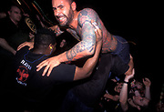A half naked man covered in tattoos is man-handled by a bouncer, U.K, 2000s.
