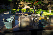 Contemporary bronze sculptures by Koko Rico of handbags and holdalls on table in Plaza el Gaitero, Laguardia, Rioja, Spain