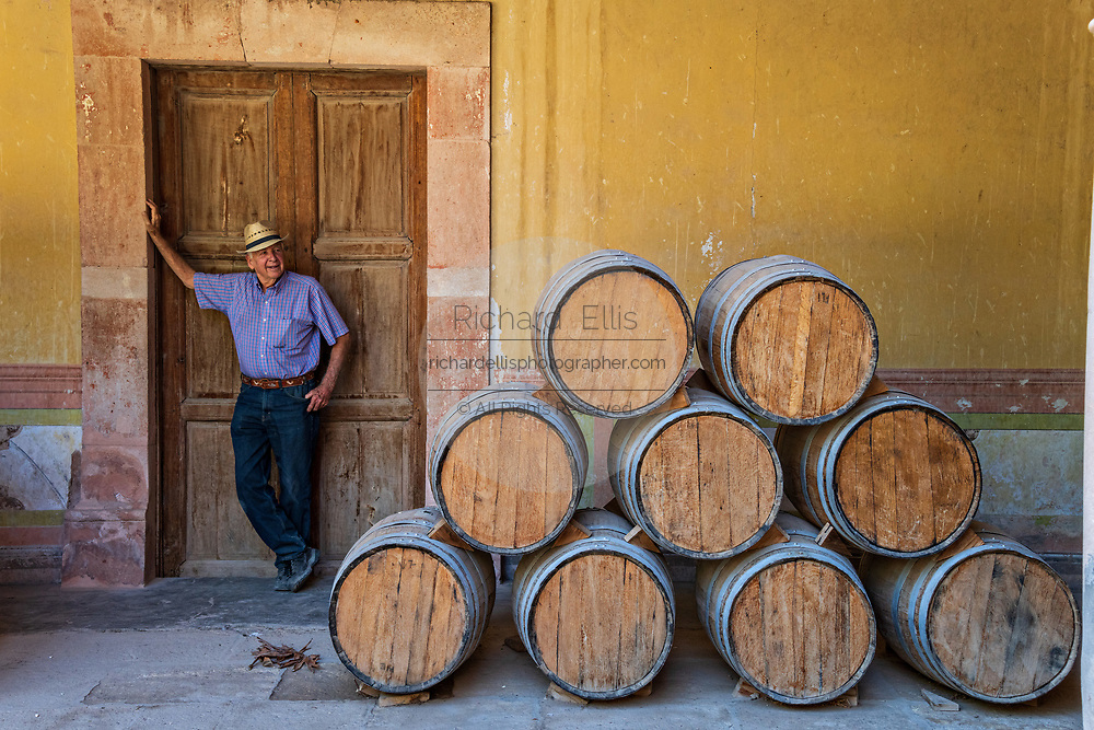 A worker rests by the oak barrels filled with Mezcal as they age under the derelict arches of the Hacienda de Jaral de Berrio in Jaral de Berrios, Guanajuato, Mexico. The abandoned Jaral de Berrio hacienda was once the largest in Mexico and housed over 6,000 people on the property and is credited with creating Mescal.