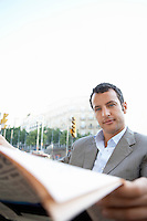 Businessman reading newspaper outdoors